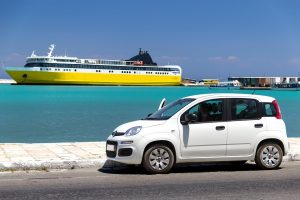 Car with cruise liner in background